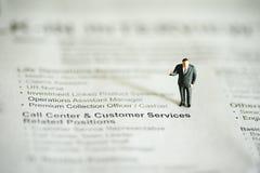 MiniaturvölkerGeschäftsmann auf Nachrichtenpapier Stockfoto