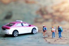Miniaturwanderer auf Karte mit Taxiauto, Konzept der Reise Stockfotografie