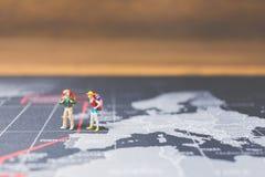 Miniaturwanderer, der auf Weltkarte geht Stockbild