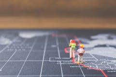 Miniaturwanderer, der auf Weltkarte geht Lizenzfreie Stockfotografie