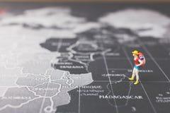 Miniaturwanderer, der auf Weltkarte geht Stockbilder