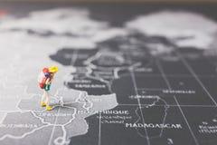 Miniaturwanderer, der auf Weltkarte geht Lizenzfreies Stockfoto