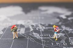 Miniaturwanderer, der auf Weltkarte geht Stockfotos