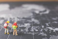 Miniaturwanderer, der auf Weltkarte geht Lizenzfreies Stockbild