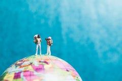 Miniaturwanderer, Reisende mit dem Rucksack, der auf Weltkarte steht Lizenzfreies Stockbild