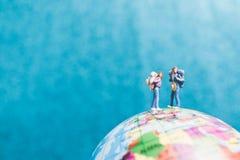 Miniaturwanderer, Reisende mit dem Rucksack, der auf Weltkarte steht Lizenzfreie Stockbilder