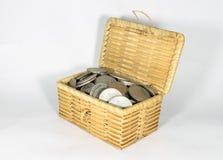 Miniaturweidenkasten füllte mit verschiedenen Münzen auf dem weißen Hintergrund und speicherte Geldkonzept lizenzfreie stockfotos
