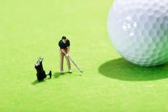 Miniaturzahl eines Golfspielers, der einen Anschlag spielt Lizenzfreie Stockfotografie