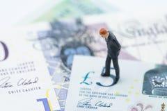 Miniaturzahl Geschäftsmannführerstellung und Denken auf 5 Pfund England-Währungsbanknoten, Brexit prüfen nach, BRITISCH lizenzfreie stockfotos