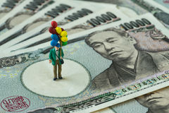 Miniaturzahl glücklicher Mann, der den Ballon steht auf Japaner hält Stockbilder