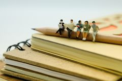 Miniaturzahl: Leute, die auf dem Stapel des Notizbuches sitzen sie Stockbilder