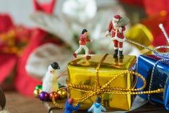 Miniaturzahl Weihnachtsmann, der auf großem goldenem anwesendem Geschenk steht Stockfotos
