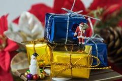 Miniaturzahl Weihnachtsmann, der auf großem goldenem Präsentkarton steht Stockbild