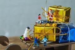 Miniaturzahl Weihnachtsmann, der auf großem Präsentkarton auf slei steht Stockbilder
