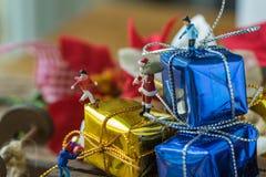 Miniaturzahl Weihnachtsmann, der auf großem Präsentkarton auf slei steht Stockfotos