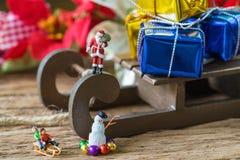 Miniaturzahl Weihnachtsmann, der auf Pferdeschlitten mit großem Geschenk steht Stockfotos