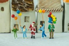 Miniaturzahl Weihnachtsmann, der mit glücklicher Familienholding steht Stockfotos