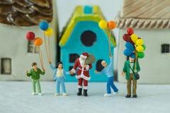 Miniaturzahl Weihnachtsmann, der mit glücklicher Familienholding steht Stockfotografie