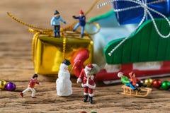 Miniaturzahl Weihnachtsmann mit dem glücklichem Kindlaufen und sta Stockfoto