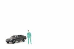 Miniaturzahlen des Mannes und des Autos Stockfoto