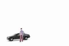 Miniaturzahlen des Mannes und des Autos Stockbilder
