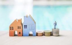 Miniatuur bedrijfsmens die zich op muntstukstapel en blokhuis bevindt over vage blauwe achtergrond Stock Afbeelding