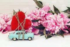 Miniatuur blauwe stuk speelgoed auto die een hart en roze pioenen op dragen Royalty-vrije Stock Afbeelding