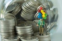 Miniatuur de holdingsballon die van de cijfer oude mens zich op muntstukken bevinden, mone Stock Afbeeldingen