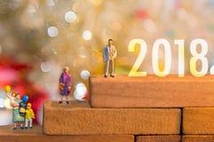 Miniatuur de holdingsballons die van de groeps gelukkige familie zich op houten 2018 met partij gelukkig nieuw jaar bevinden royalty-vrije stock foto's