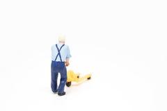 Miniatuur de mensenconcept van de mensenlevering op witte achtergrond met a Royalty-vrije Stock Afbeelding