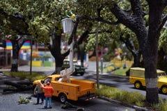 Miniatuur het snoeien boom en besnoeiingsbladeren op weg Arbeiderstribunes op vrachtwagenkraan stock afbeeldingen