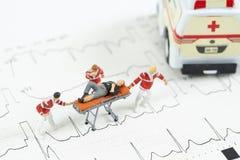 Miniatuur het vervoerpatiënt van het gezondheidszorgteam aan ziekenwagenauto stock foto's