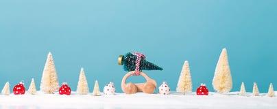 Miniatuur houten auto die een Kerstboom dragen Royalty-vrije Stock Afbeeldingen
