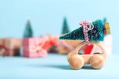 Miniatuur houten auto die een Kerstboom dragen Royalty-vrije Stock Afbeelding