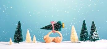 Miniatuur houten auto die een Kerstboom dragen Stock Afbeelding