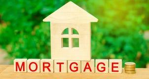 Miniatuur Huis en Money Houten blokken en de inschrijvings` hypotheek ` krediet voor bezit/flat Bedrijfsleningen voor echt stock foto
