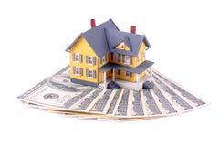 Miniatuur huis over geïsoleerdl geld Stock Foto's
