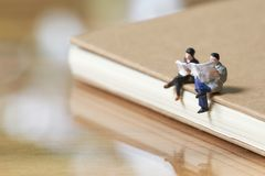 Miniatuur 2 mensen die Gelezen krant op Notaboek zitten die als achtergrond bedrijfsconcept gebruiken royalty-vrije stock fotografie