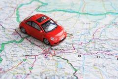 Miniatuur rode auto over de kaart van Bulgarije Stock Foto