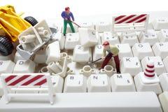 Miniatuur stuk speelgoed arbeiders die computertoetsenbord herstellen Stock Foto