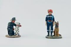 Miniatuur van brandweerlieden en hun honden stock foto's