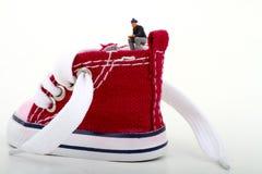 Miniatuur van een jongenszitting op een tennisschoen Stock Foto