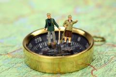Miniatuur wandelaars die zich op een kompas bevinden. Royalty-vrije Stock Afbeelding