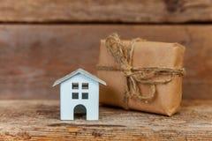 Miniatuur witte stuk speelgoed huis en giftdoos op houten achtergrond royalty-vrije stock foto