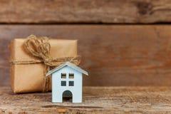 Miniatuur witte stuk speelgoed huis en giftdoos op houten achtergrond stock afbeeldingen