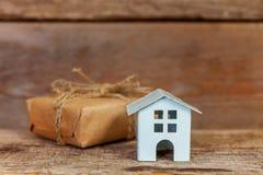 Miniatuur witte stuk speelgoed huis en giftdoos op houten achtergrond royalty-vrije stock foto's