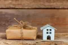 Miniatuur witte stuk speelgoed huis en giftdoos op houten achtergrond royalty-vrije stock fotografie