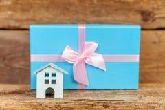 Miniatuur witte stuk speelgoed huis en giftdoos op houten achtergrond stock fotografie