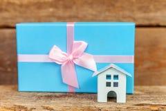 Miniatuur witte stuk speelgoed huis en giftdoos op houten achtergrond royalty-vrije stock afbeelding