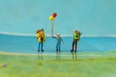 Miniatuurbackpackers met de gelukkige impulsen die van de mensenholding zich bevinden Stock Foto